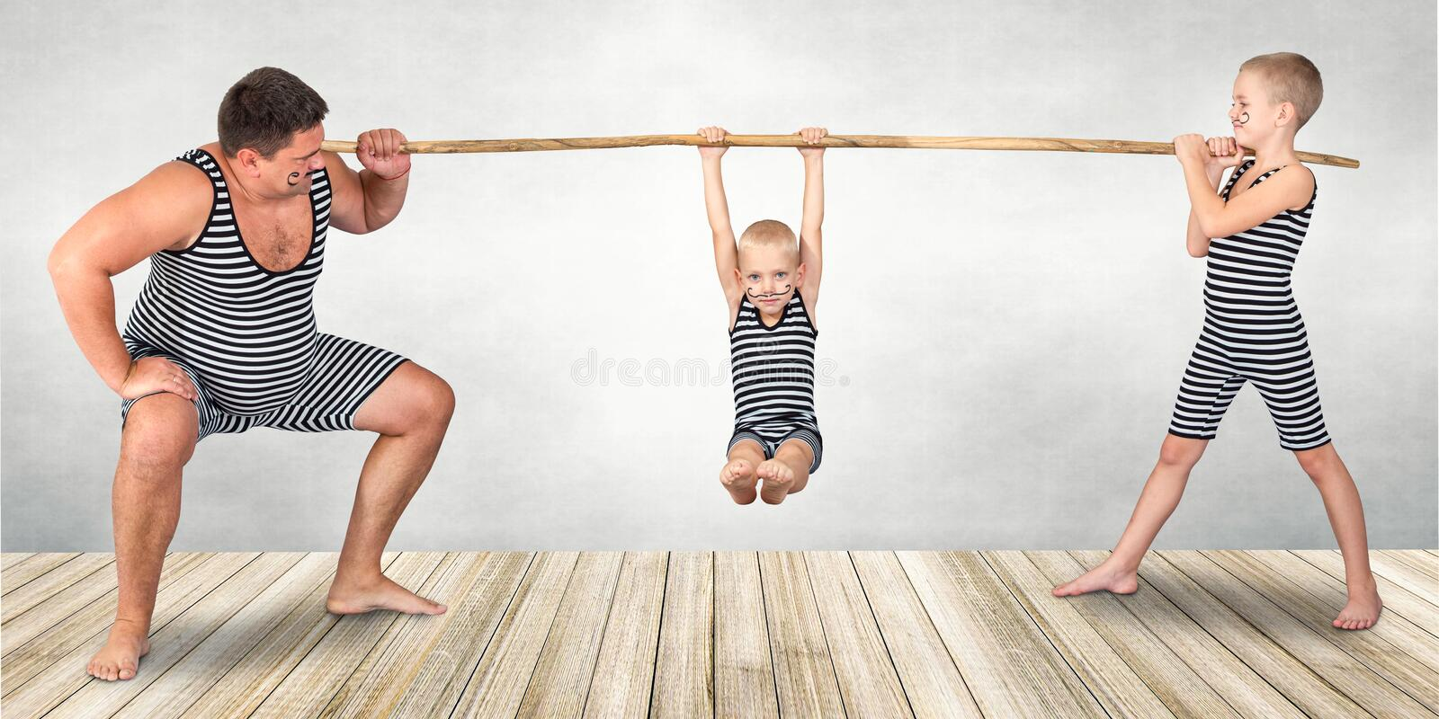 Family of strongman. The father of two sons in vintage costume of athletes perform strength exercises. Family look. stock photos