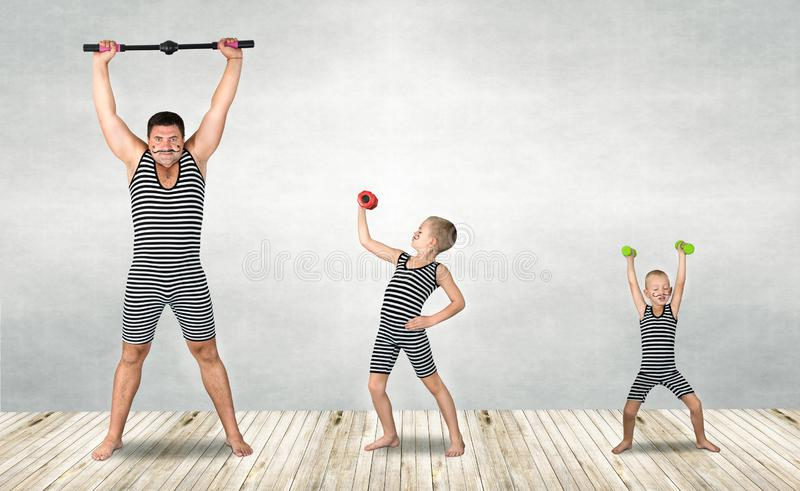 Family of strongman. The father of two sons in vintage costume of athletes perform strength exercises. Family look. royalty free stock images
