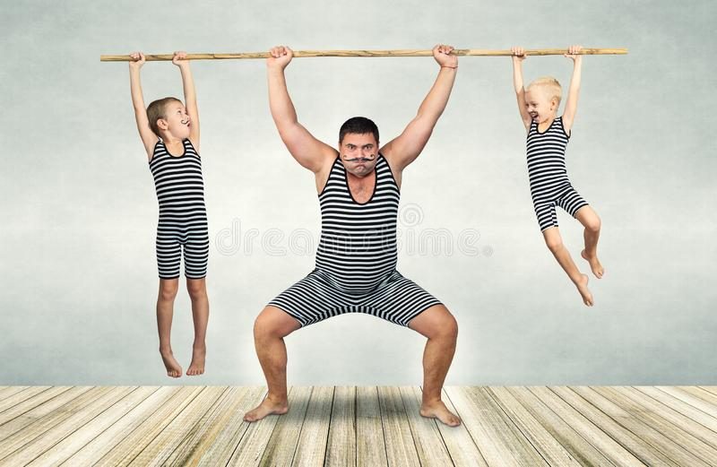 Family of strongman. Father and two sons in vintage costumes drag the rope. Family look. royalty free stock photos