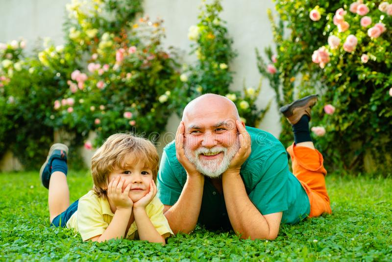 Family summer and active holidays. Father and grandfather. Cute child boy hugging his grandfather. Happy father and son stock photo