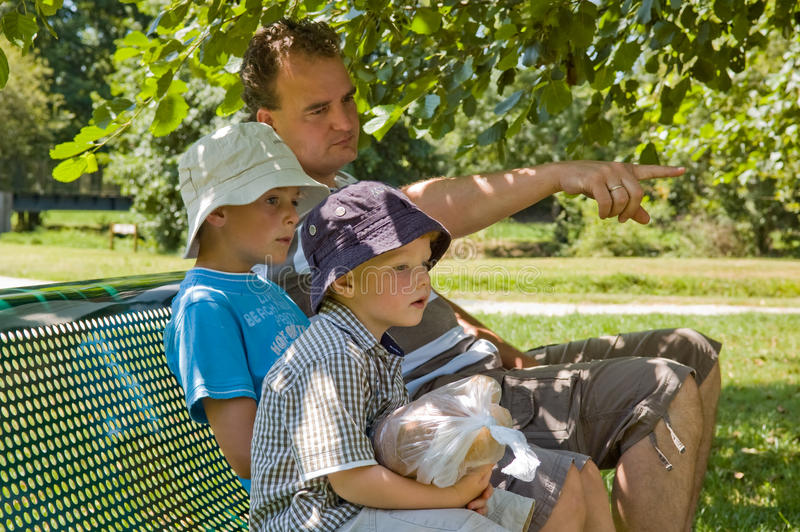 Family in summer time. Father and two kids sitting on a shaded bench on a hot summer day. Father poiting out something to his sons (8 and 3 royalty free stock images