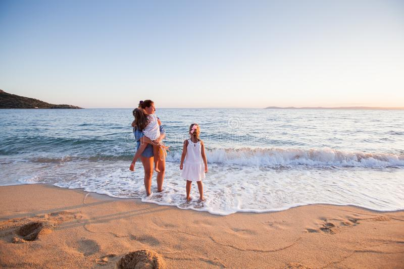 Family summer travel. Happy Family summer travel vacation, mother with daughters enjoying sunset on sand beach royalty free stock images