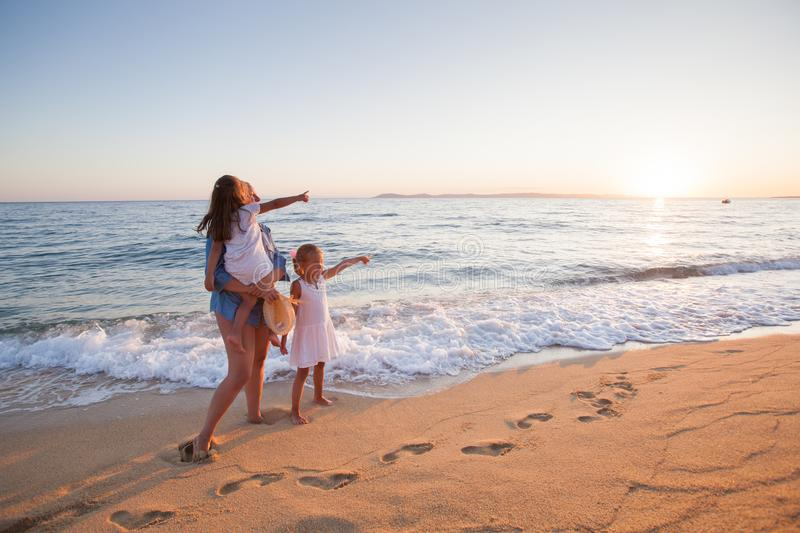 Family summer travel. Vacation, mother with daughters enjoying sunset on sand beach royalty free stock image