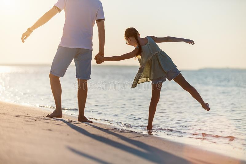 Family at sunset. Father and little daughter on beach at sunset royalty free stock images