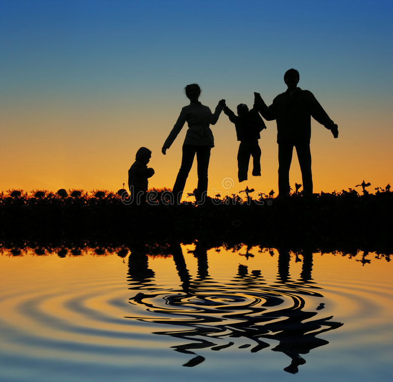 Family on sunset pond