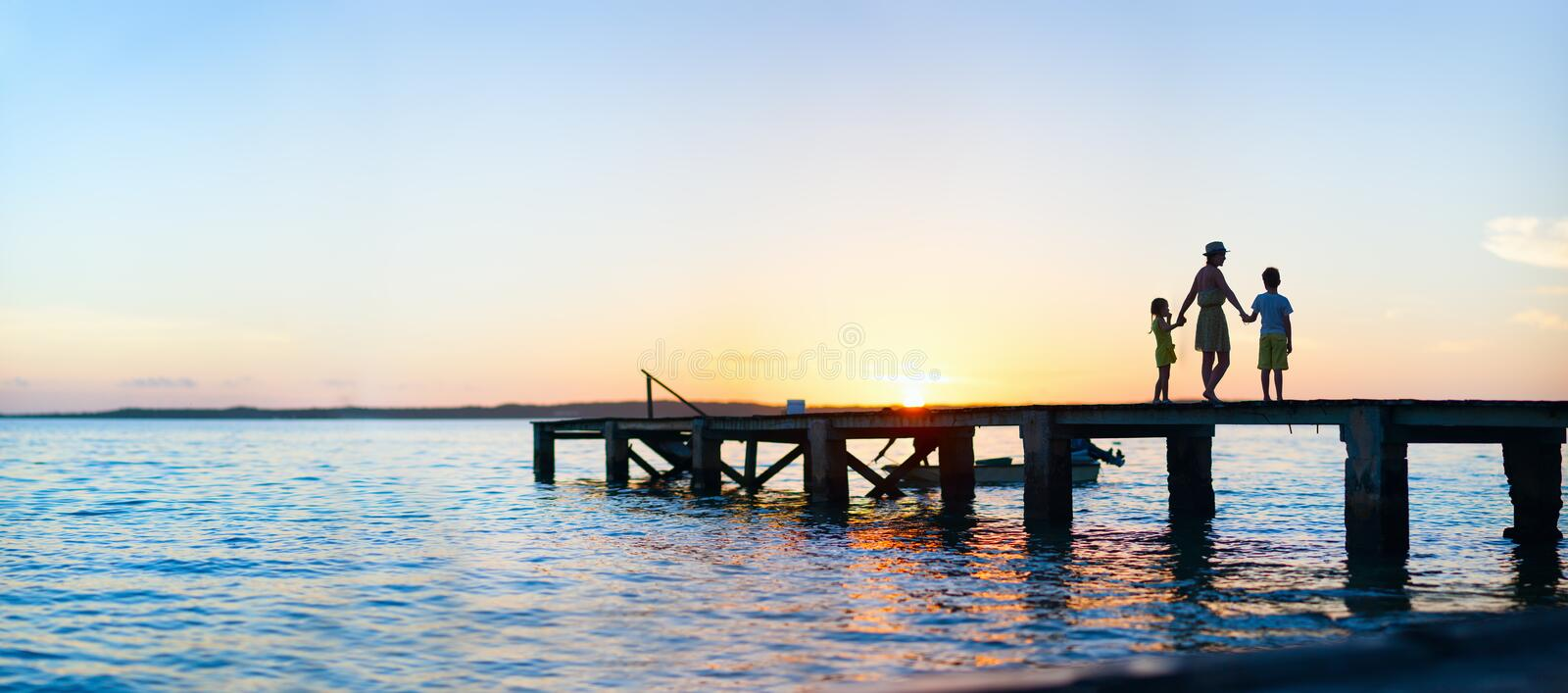 Family sunset silhouettes. Family silhouettes on a bridge at sunset stock photos
