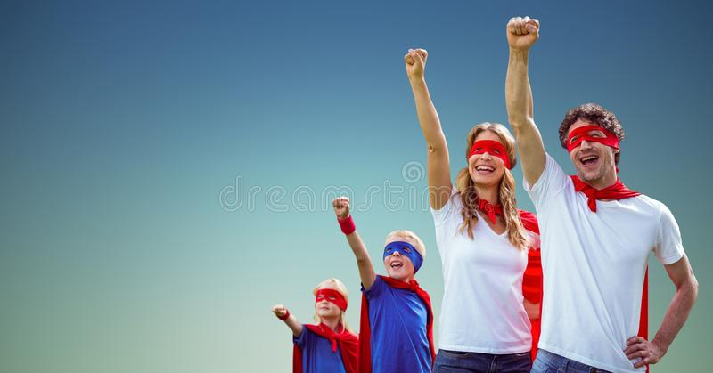 Family in superhero costumes standing with arms raised stock photo