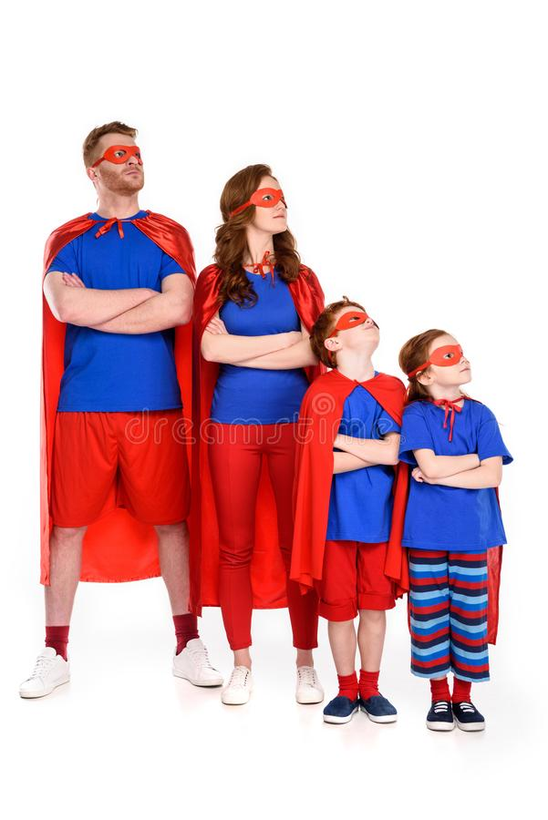 family of superheroes in costumes standing with crossed arms and looking away royalty free stock photos