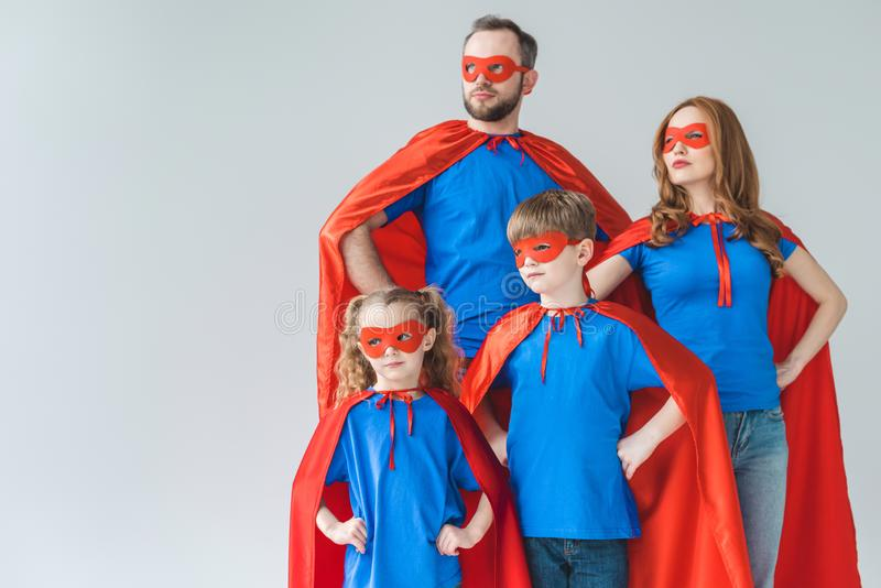 family of superheroes in costumes standing with hands on waist and looking away stock images