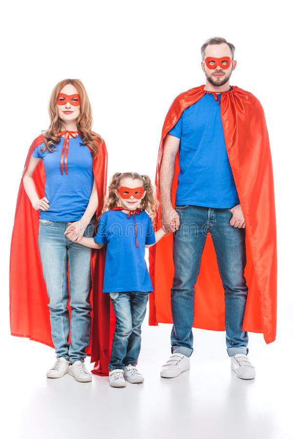family of superheroes holding hands and looking at camera stock images