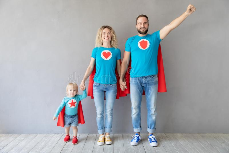 Family of superheroes playing at home stock image