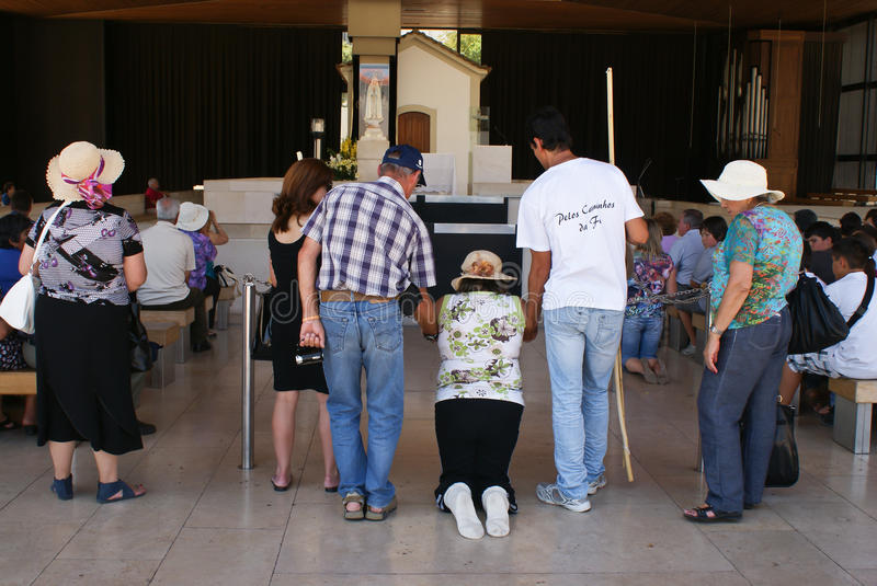 Family supporting kneeling pilgrim in Fatima royalty free stock images