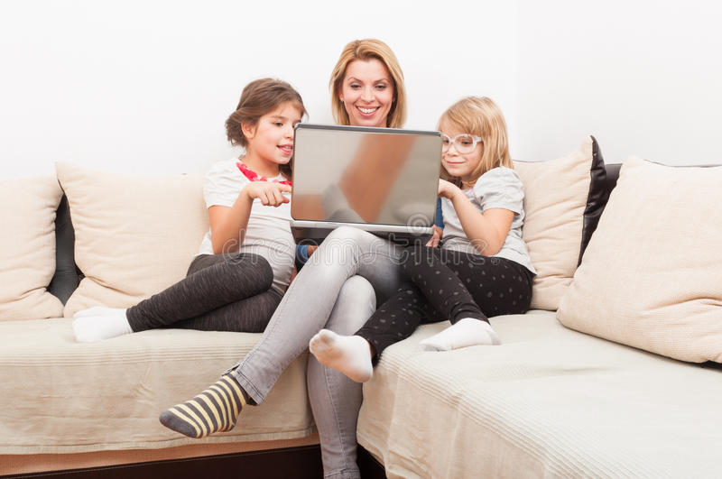 Family surfing or browsing internet together. Using laptop relaxed on the sofa or couch stock photos