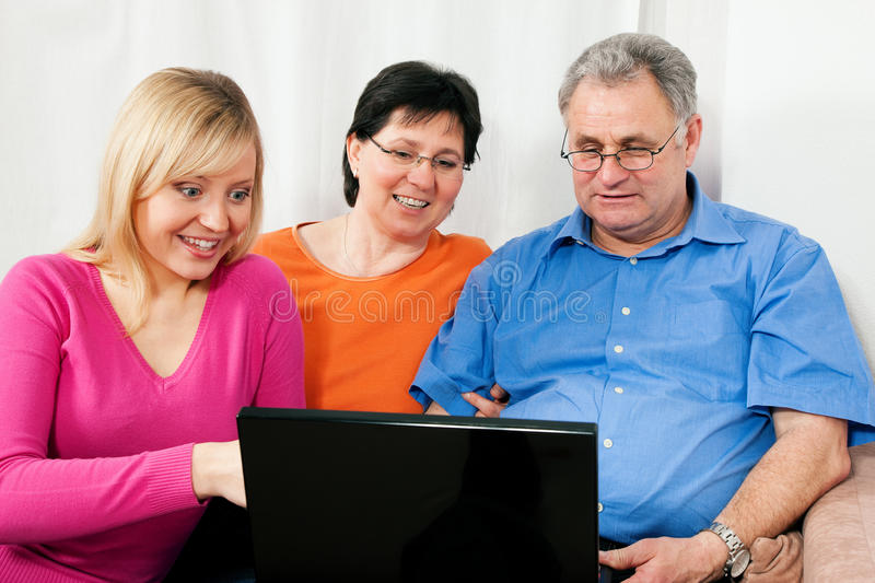 Family surfing the internet. Family (parents and adult daughter) surfing the internet using a laptop computer royalty free stock photography