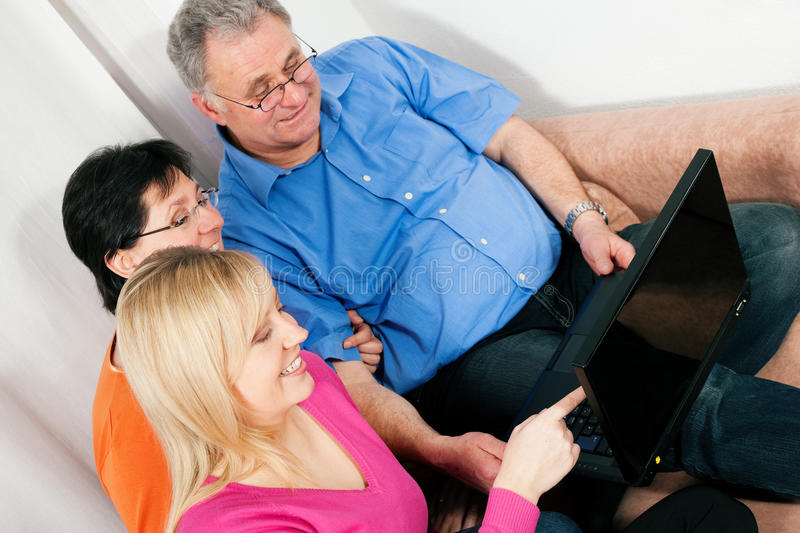 Family surfing the internet. Family (parents and adult daughter) surfing the internet using a laptop computer stock image