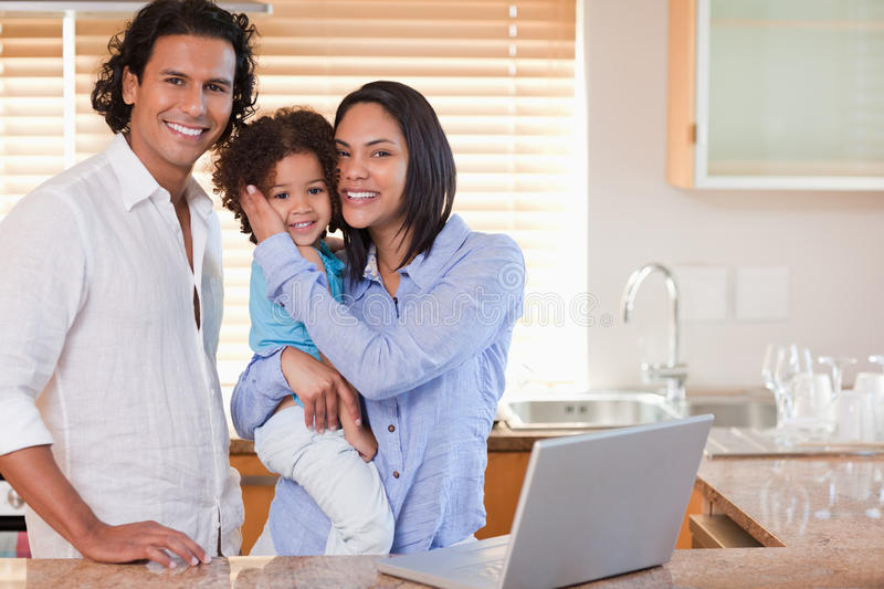 Family surfing the internet. Young family surfing the internet in the kitchen together stock photo