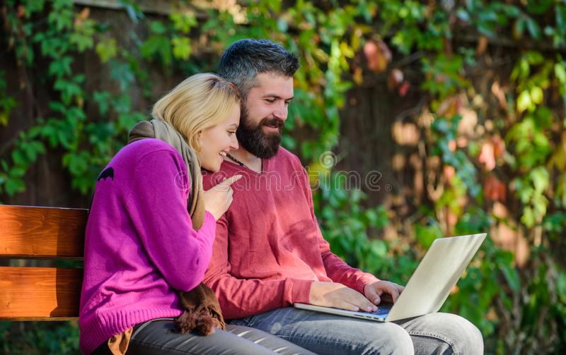 Family surfing internet for interesting content. Couple in love notebook consume content. Internet surfing concept. Couple with laptop sit bench in park nature royalty free stock images