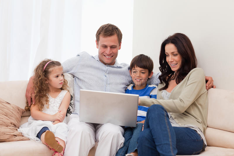 Family surfing the internet together. Young family surfing the internet together royalty free stock photo