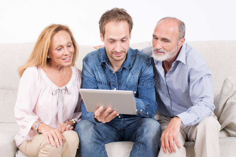 Family surfing in internet. Younger men with elderly persons checking an electronic devise royalty free stock image