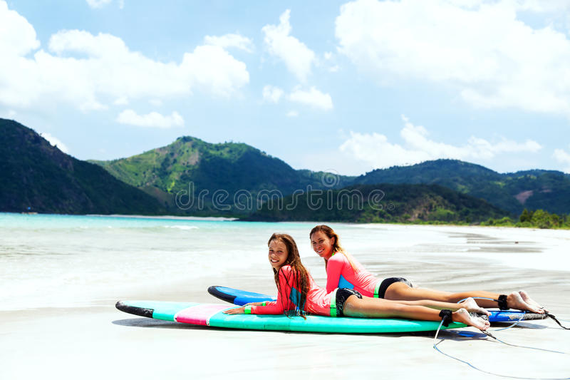 Family surfing. Mom with child are learning surfing together stock photo
