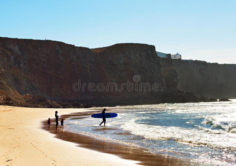 Family surfing, Portugal. Surfers family on the beach in the bright sunny day. Portugal royalty free stock image