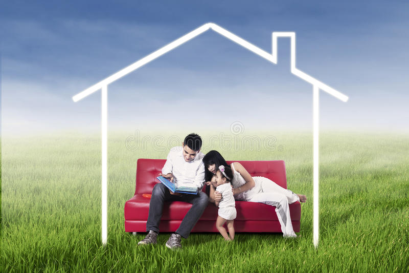 Family surrounded by home drawing. Happy family relaxing on couch surrounded by home drawing in meadow royalty free stock image