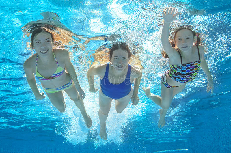 Family swim in pool or sea underwater, mother and children have fun in water. Family swim in pool or sea underwater, happy active mother and children have fun in stock photo