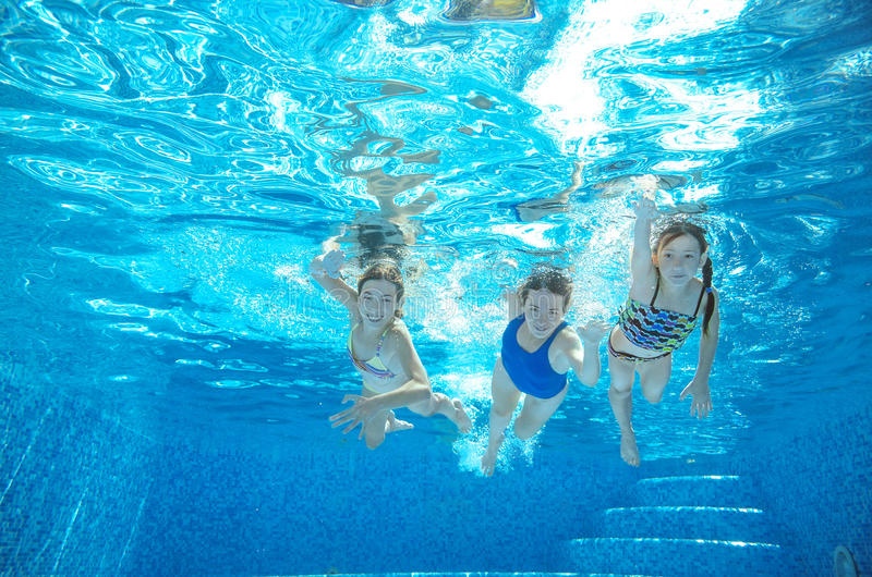 Family swim in pool or sea underwater, mother and children have fun in water. Family swim in pool or sea underwater, happy active mother and children have fun in stock photography
