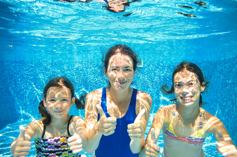 Family swim in pool underwater, mother and children have fun in water,. Family swim in pool underwater, happy active mother and children have fun in water, kids royalty free stock images