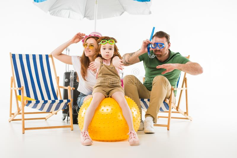 Family in swimming goggles depicting swim with sunshade, sun loungers and ball. Isolated on white, travel concept stock photo