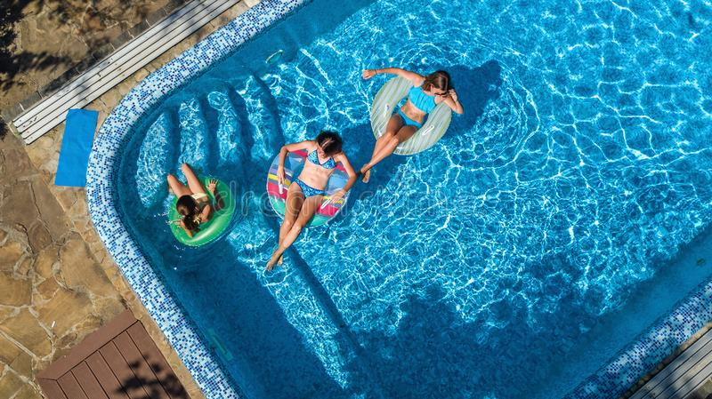 Family in swimming pool aerial drone view from above, happy mother and kids swim on inflatable ring donuts and have fun in water. On family vacation, tropical royalty free stock photo