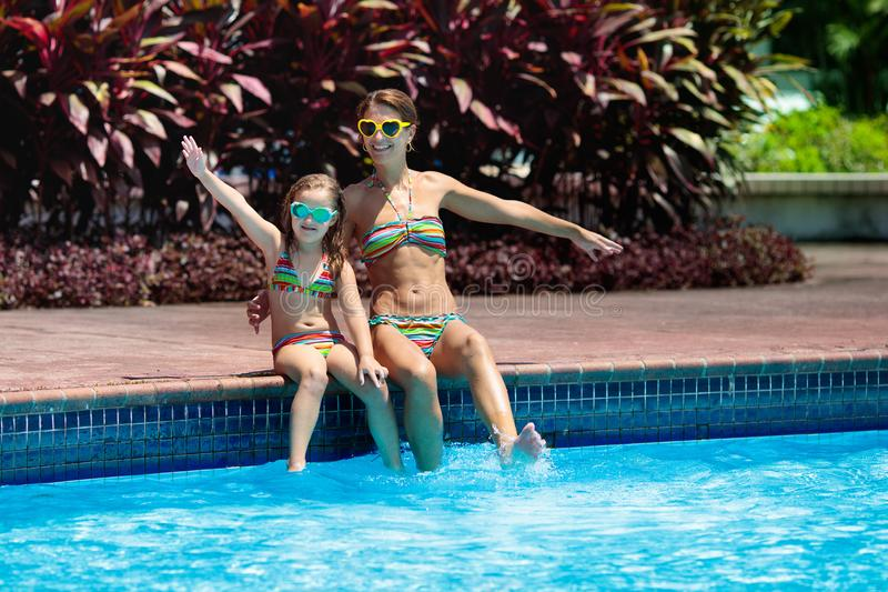 Family in swimming pool. Mother and child swim stock photography