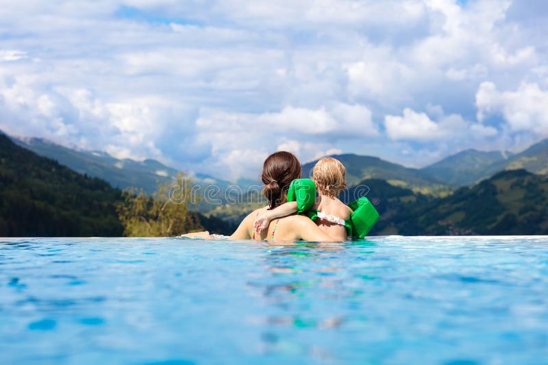 Family in swimming pool with mountain view royalty free stock photos