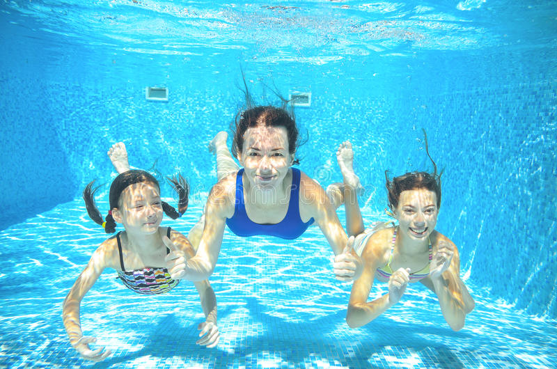 Family swims in pool underwater, happy active mother and children have fun. Kids sport on vacation royalty free stock photo