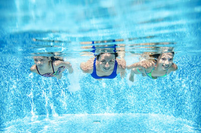 Family swims in pool underwater, happy active mother and children have fun under water, fitness and sport with kids stock images