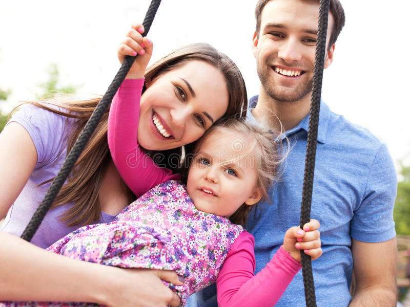 Family on a swing. Happy family with little girl outdoors