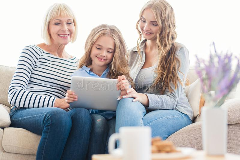 Family with tablet computer at home on sofa stock photo