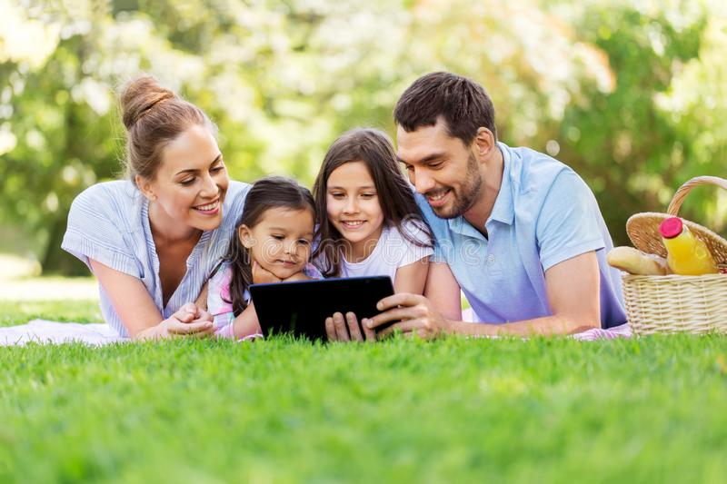 Family with tablet pc on picnic in summer park royalty free stock photo