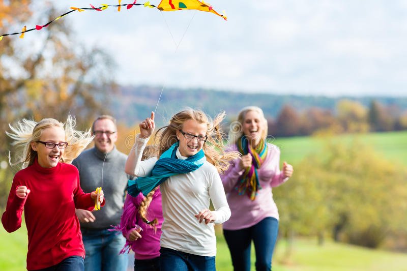 Family take walk in autumn forest flying kite. Happy family take walk in autumn forest flying kite royalty free stock photo