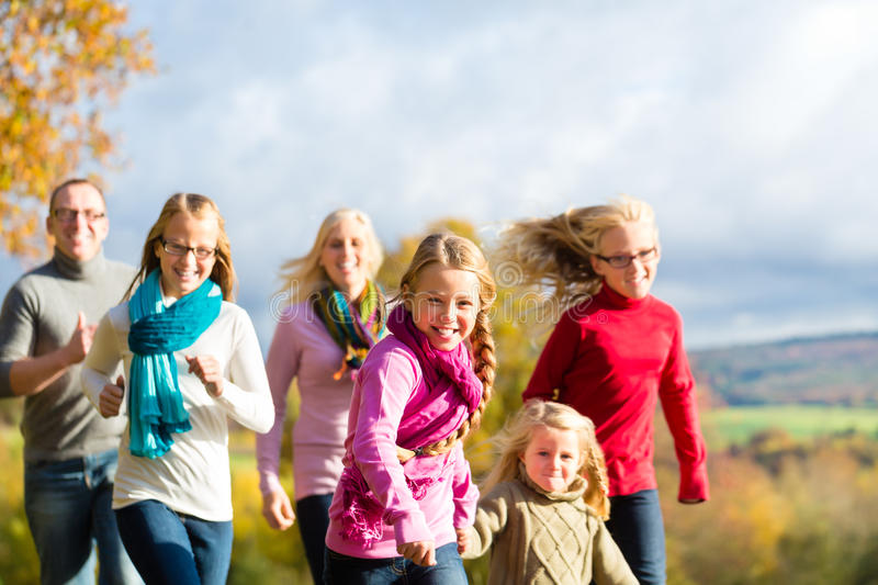 Family take a walk in autumn forest. Girls running ahead at family walk through the park in fall or autumn stock images