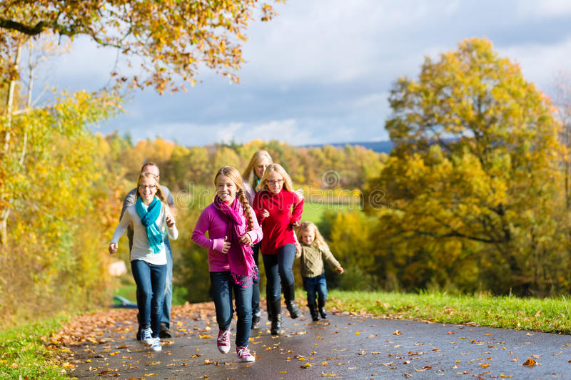 Family take a walk in autumn forest. Girls running ahead at family walk through the park in fall or autumn stock photos