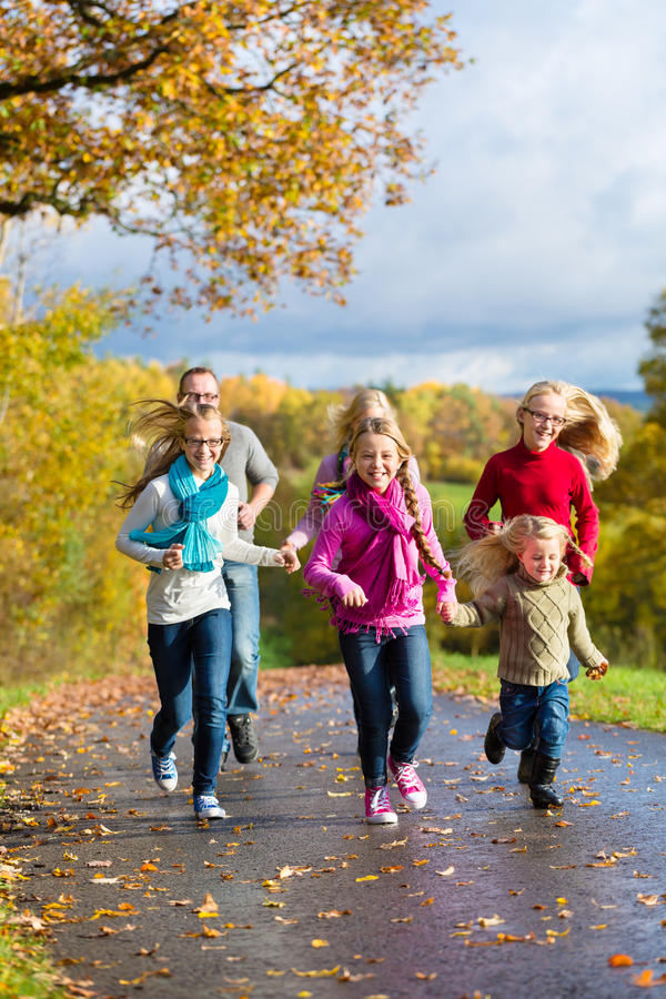 Family take a walk in autumn forest. Girls running ahead at family walk through the park in fall or autumn royalty free stock photography