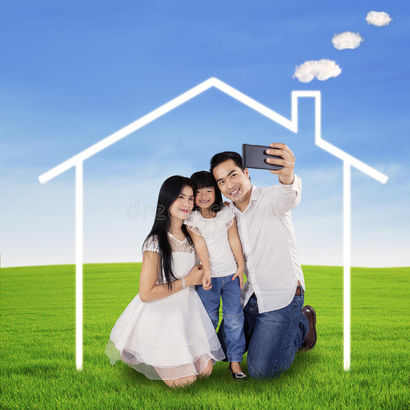 Family taking picture under a dream house. Portrait of happy family using a mobilphone to take self portrait under a dream house symbol stock images