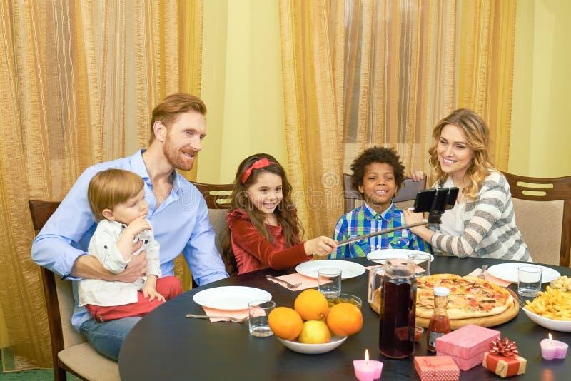 Family taking selfie, dinner table. stock photos