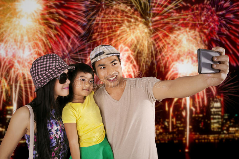 Family taking selfie photo in the fireworks festival. Happy family using mobile phone to take selfie picture in the fireworks festival at the new year stock photography
