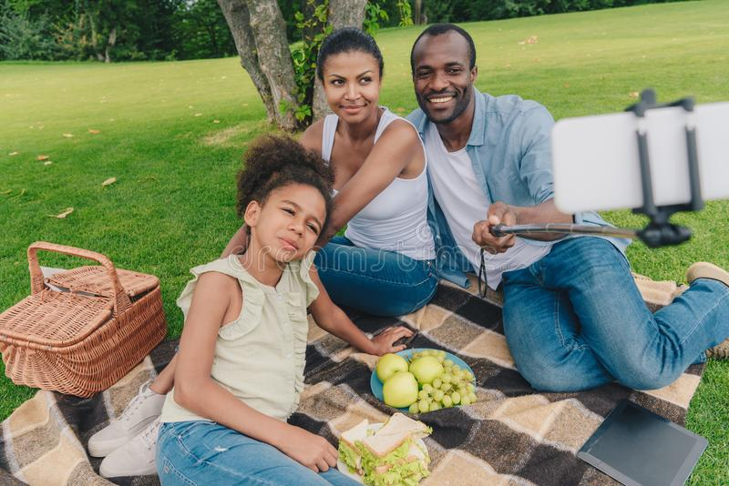 Family taking selfie. Young african american family taking selfie while resting together during picnic in park royalty free stock images
