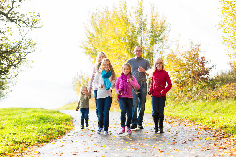 Family taking walk in autumn forest. Girls going ahead at family walk through the park in fall or autumn royalty free stock photo