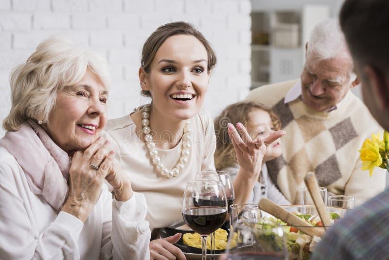 Family talking and enjoying dinner stock image