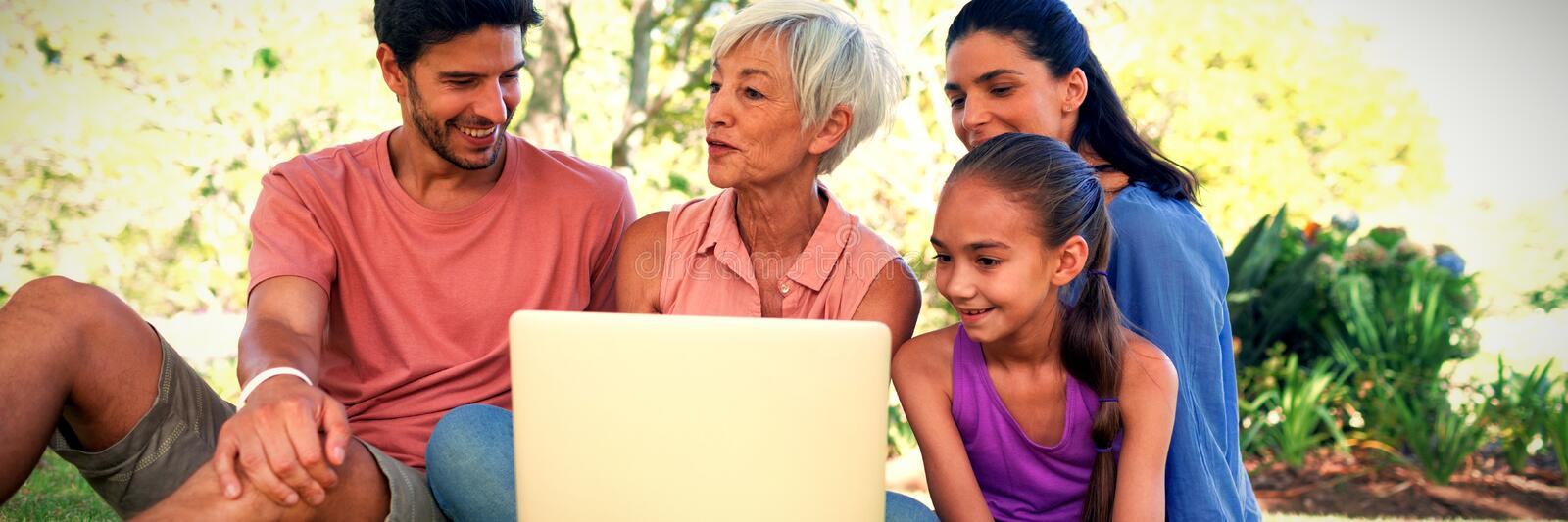 Family talking while using laptop in the park royalty free stock images