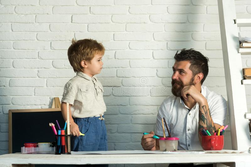 Family team, the father is engaged with his son drawing. A stylish bearded man and his little son. Responsible parent. Family team, the father is engaged with stock image